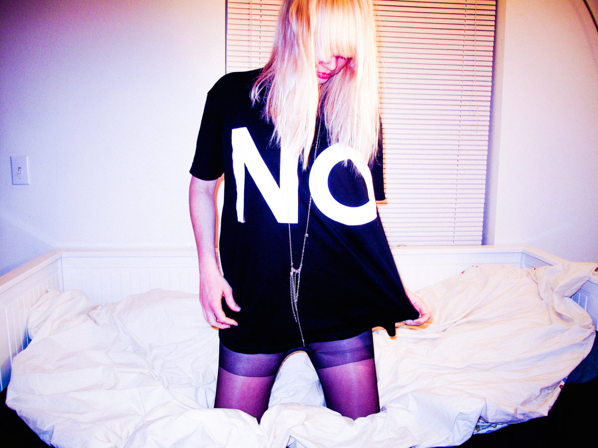 """A photograph of EMA kneeling on an unkempt bed with a black t-shirt with big white letters spelling """"NO."""""""
