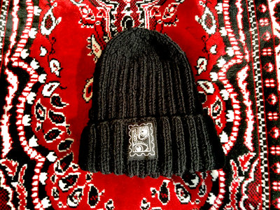 "Hand-knitted hat with ""Suck Puck Stamp"" print. main photo"