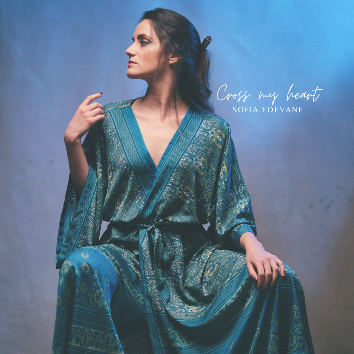 Cover art for Sofia's EP. Sofia sits poised against a blue background, wearing a green and gold gown. She has her right arm against her shoulder and she looks off to the right.'